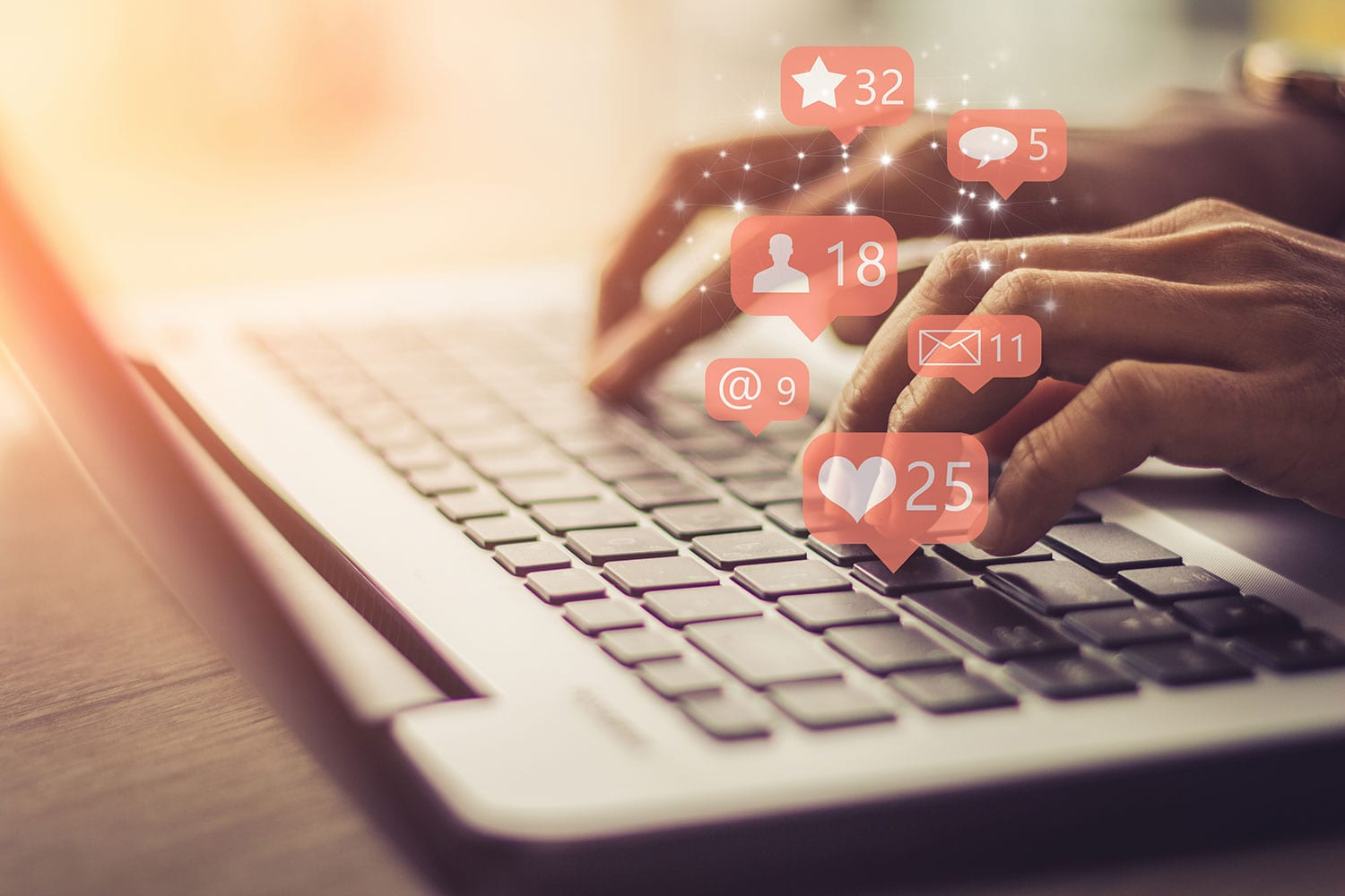 B2B social media presence, person typing on a laptop with social media likes and notification icons on keyboard